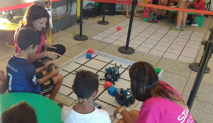 Niños y adultos jugando con robots