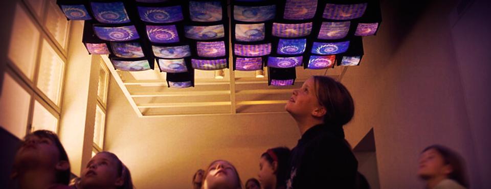 Niños mirando pantallas colgadas en el techo